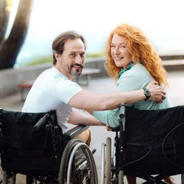 men_and_woman_in_wheelchair_holding_together.jpeg