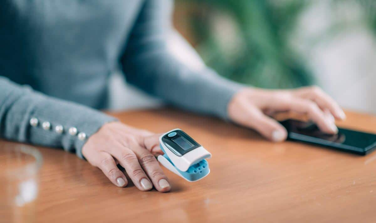 Senior Woman Using Pulse Oximeter and Smart Phone, Measuring Oxygen Saturation