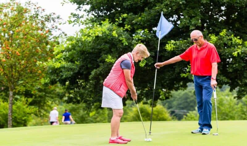 senior man and woman playing golf after performing golf stretching exercises for seniors