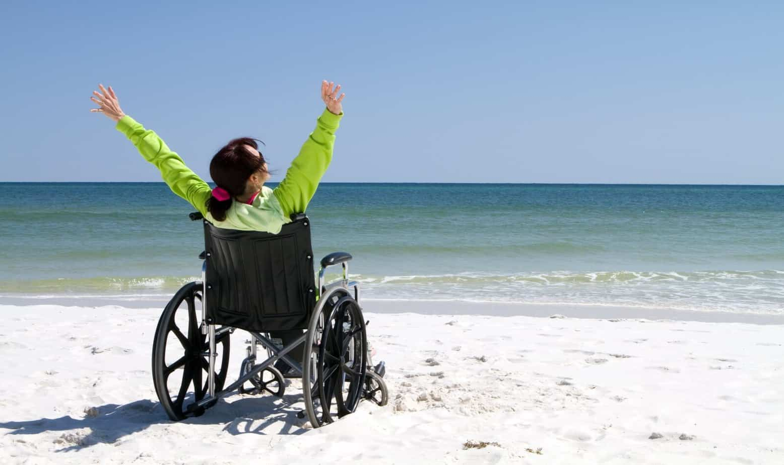 a lady with arms raised celebrates her achievement while traveling in the beach in her wheelchair