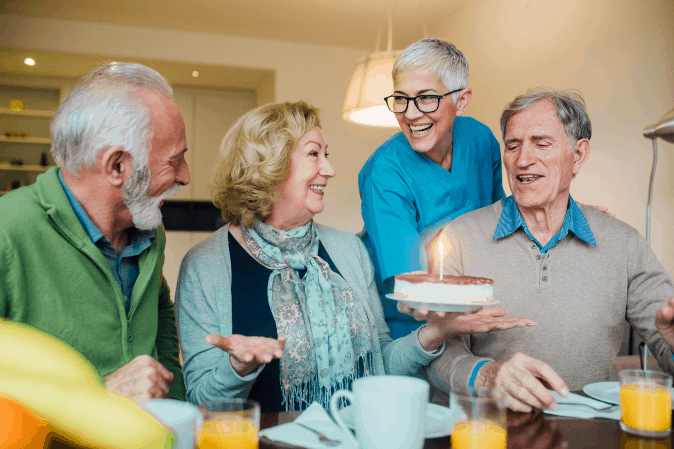 group of seniors celebrating a friend's birthday with a strawberry cake
