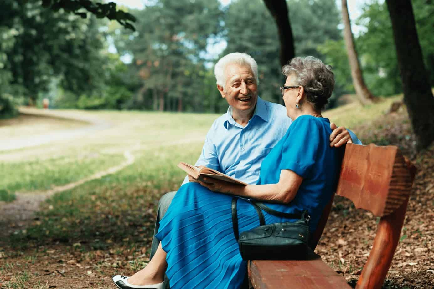 a senior couple sitting on a bench while holding their memory book