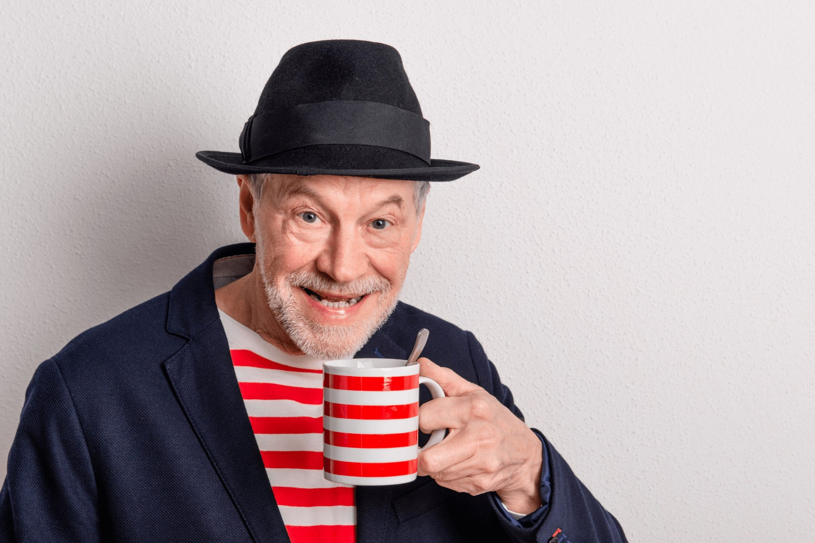 an old man wearing a striped shirt while holding a matching striped mug