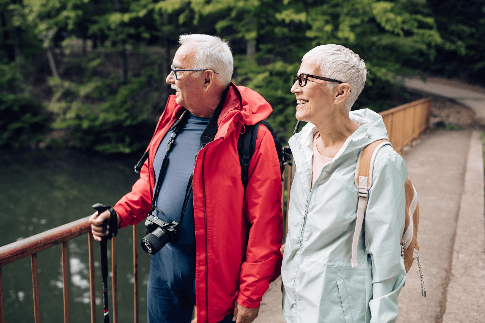 a elderly couple wearing a backpack while traveling and enjoying the lake's view
