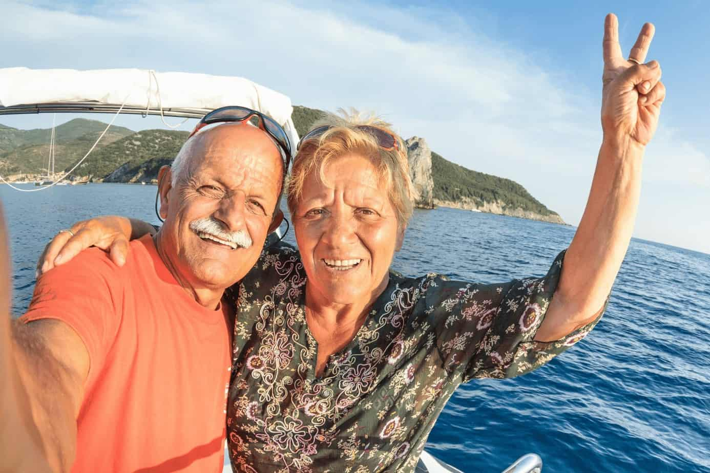a selfie photo of a senior couple while riding a boat