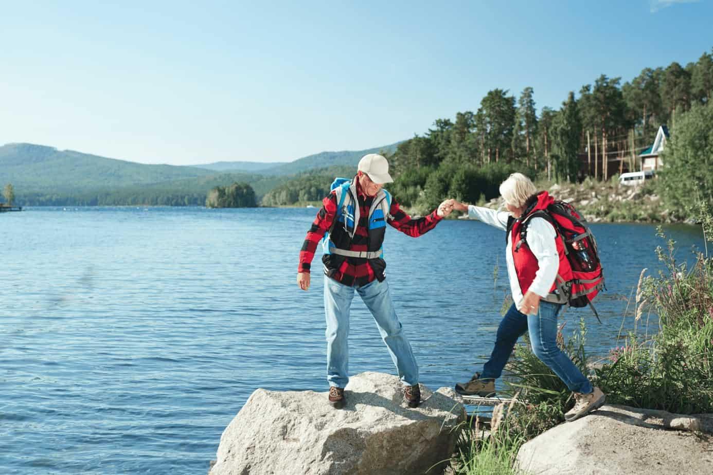 an elderly couple having an adventure on a cliff beside a beach