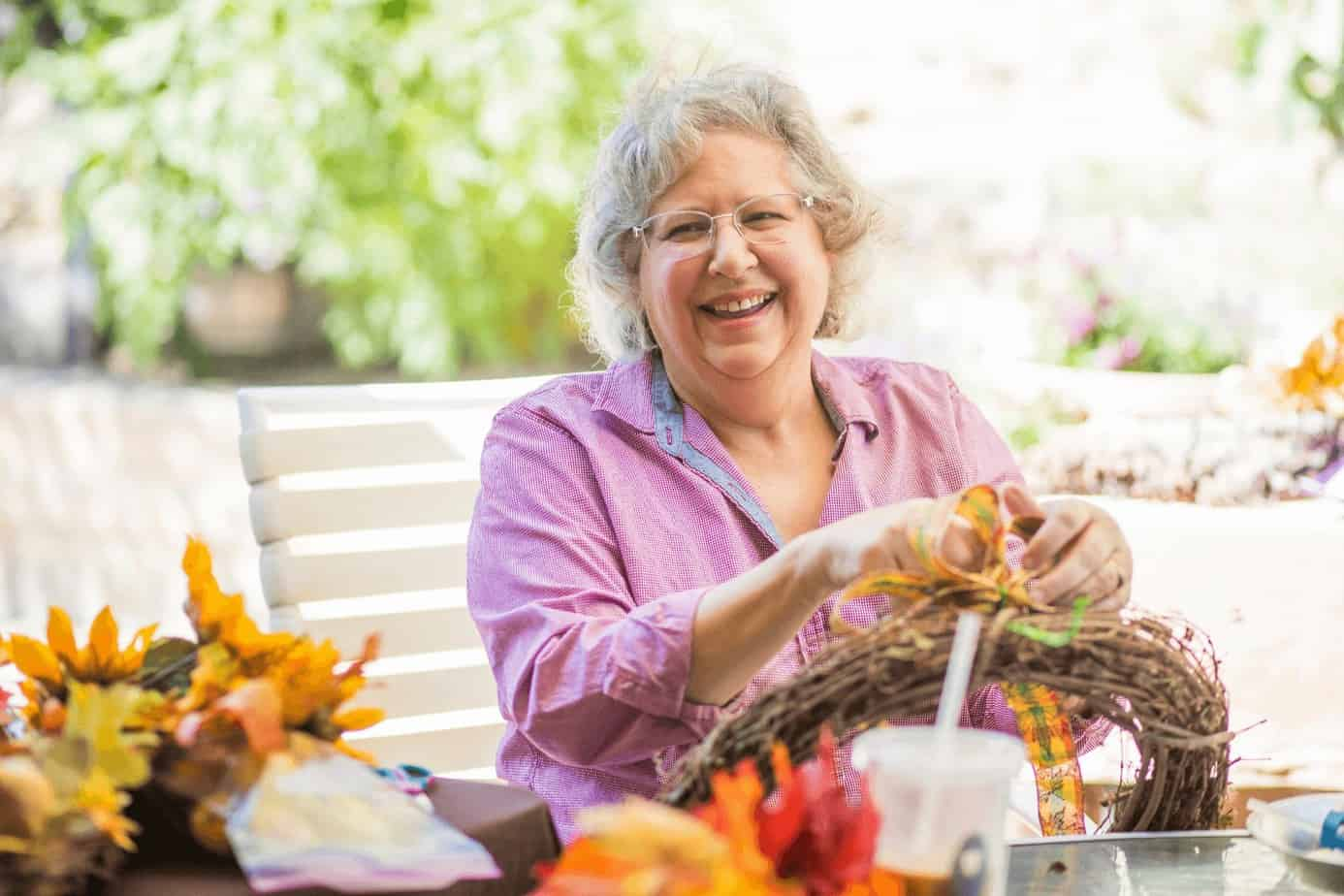 a senior woman making some crafts with her friends, one of easy activities for Alzheimer's