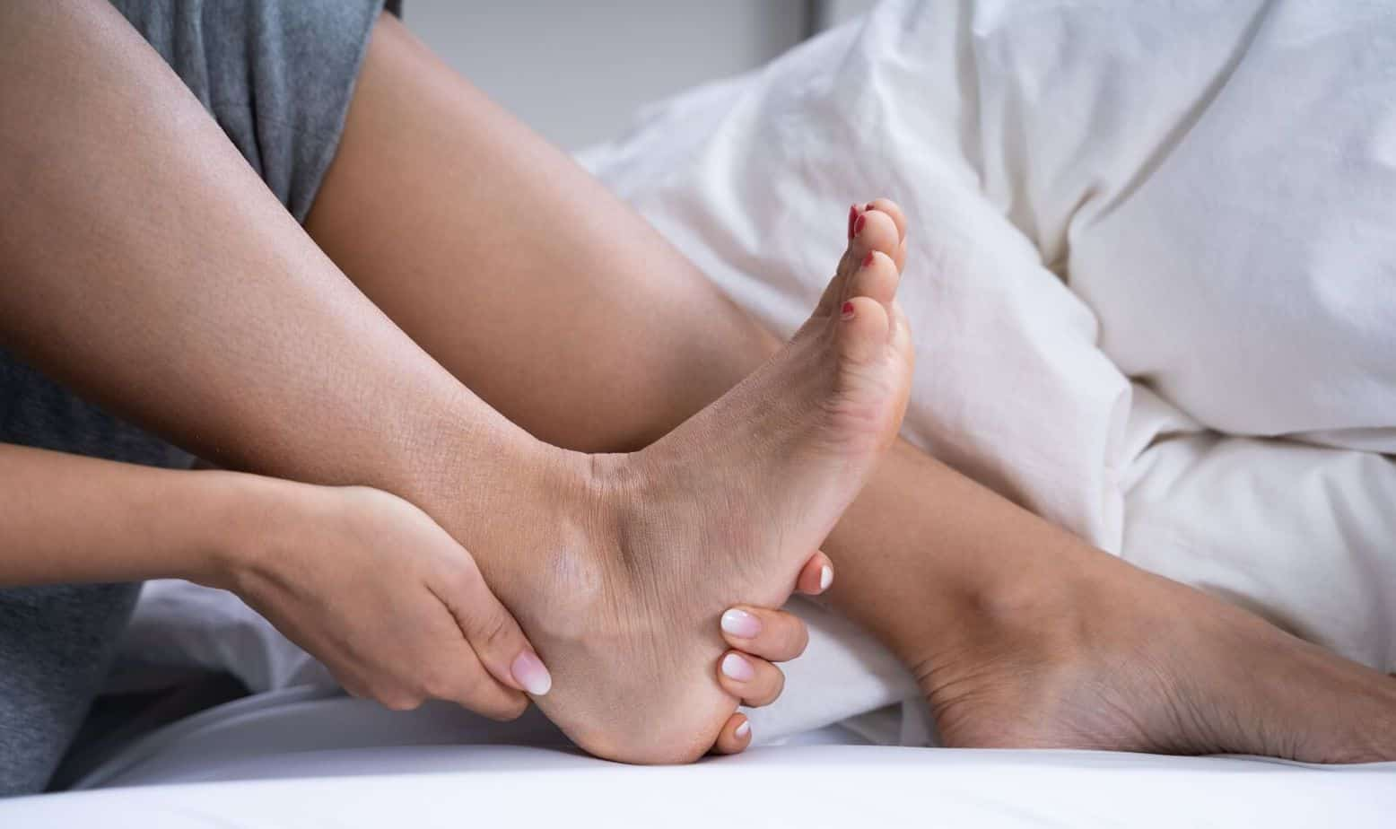 Woman Feeling Achilles Heel Pain in her aging feet