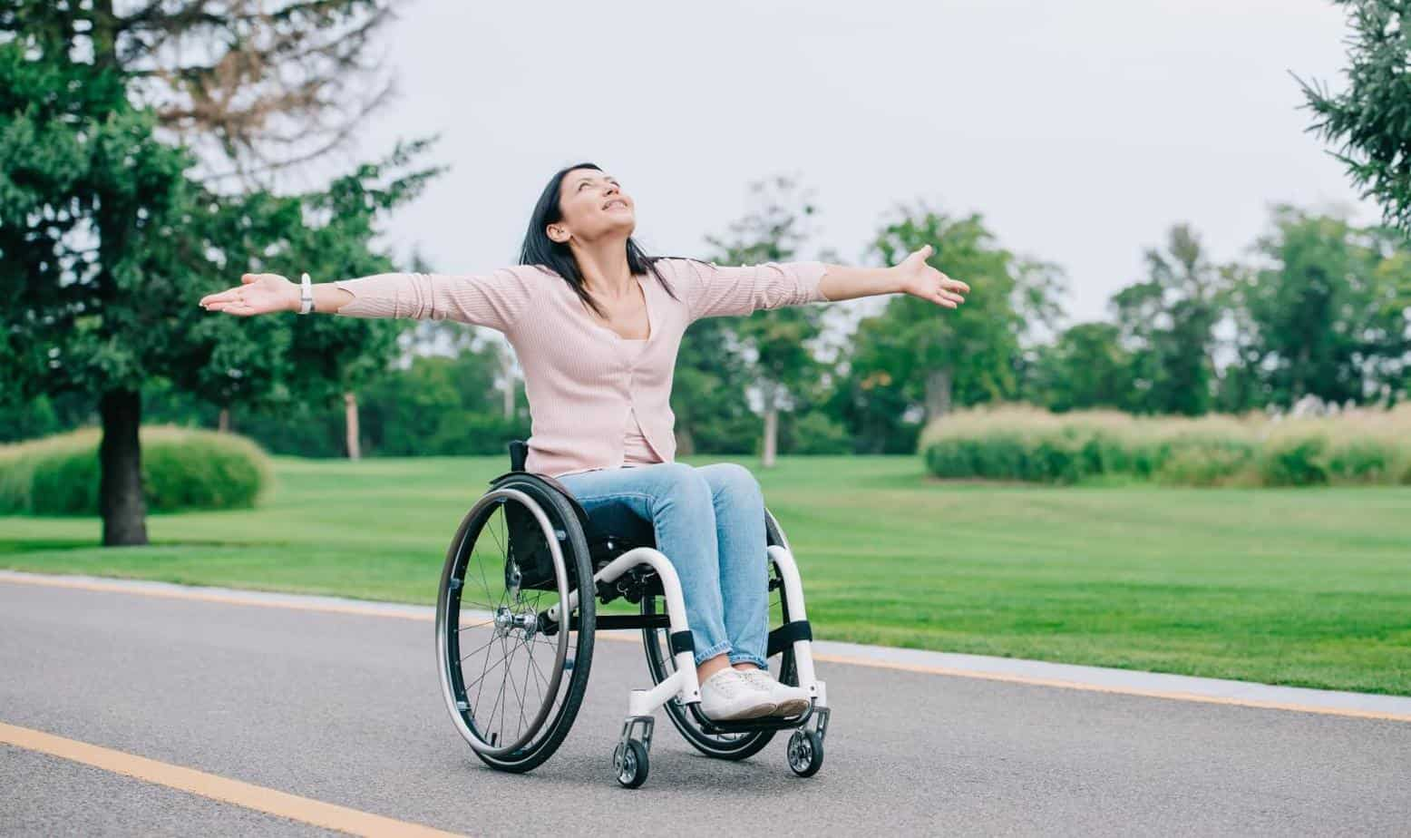 Happy disabled woman in transport wheelchair gesturing while looking at clear sky