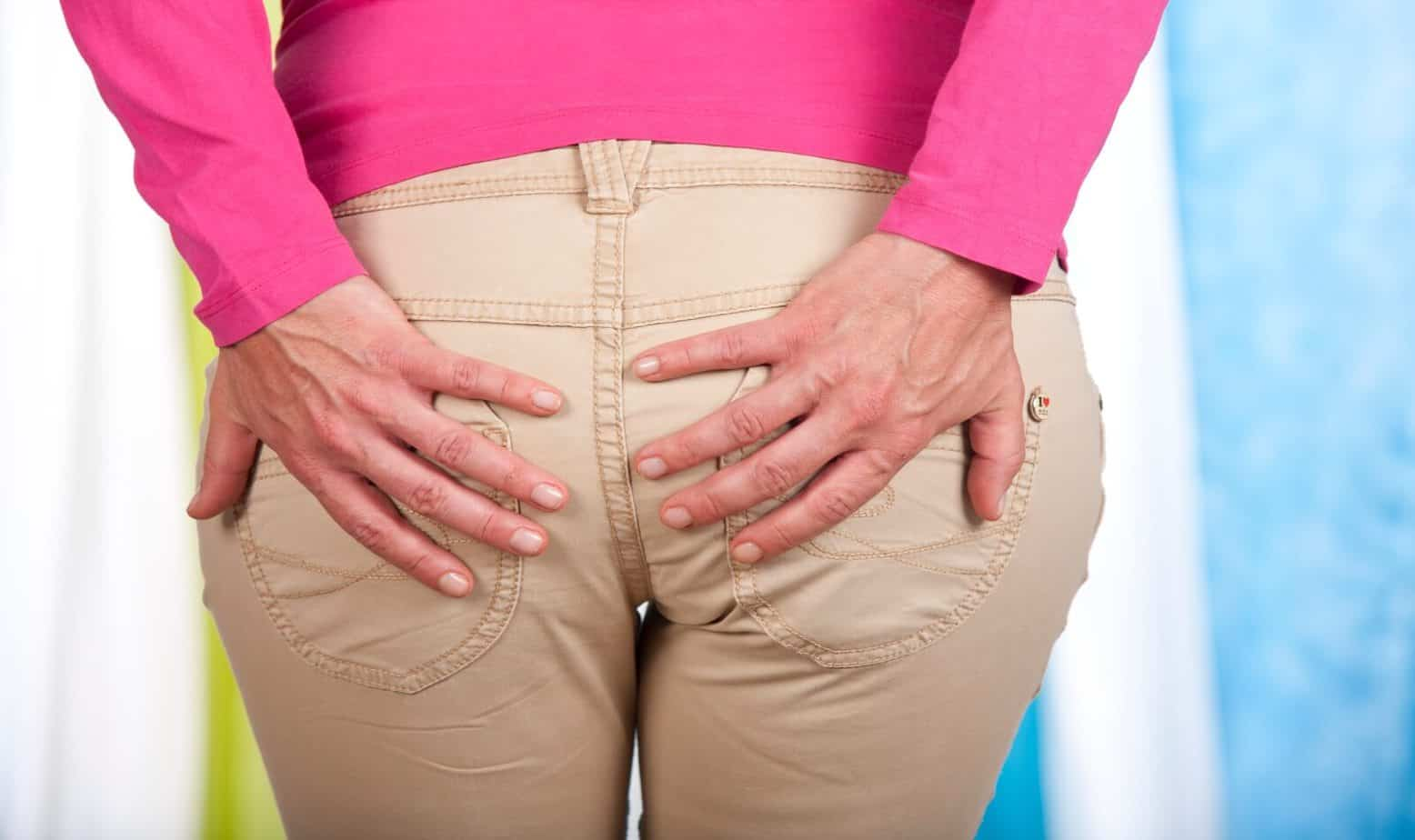 a woman holding her buttocks in pain