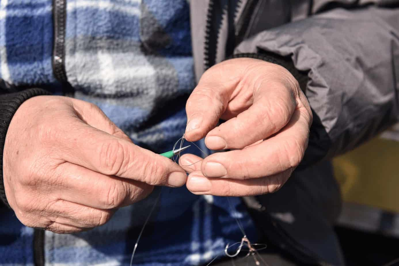 a close-up shot of a man's hand untying a knot