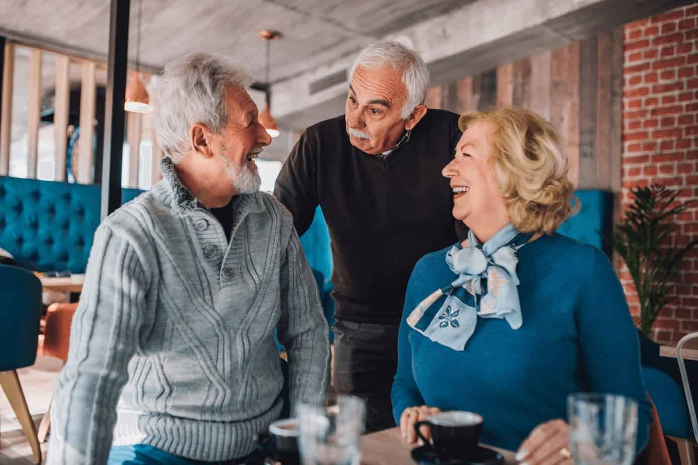 two old men talking to a beautiful old lady while drinking coffee