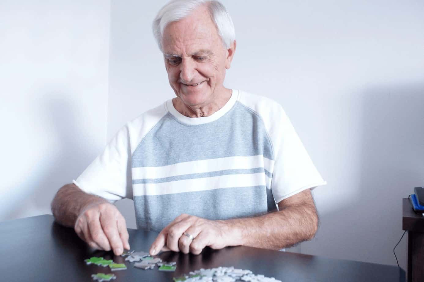 a senior man solving puzzle on a table, one of the easy activities for alzheimer's