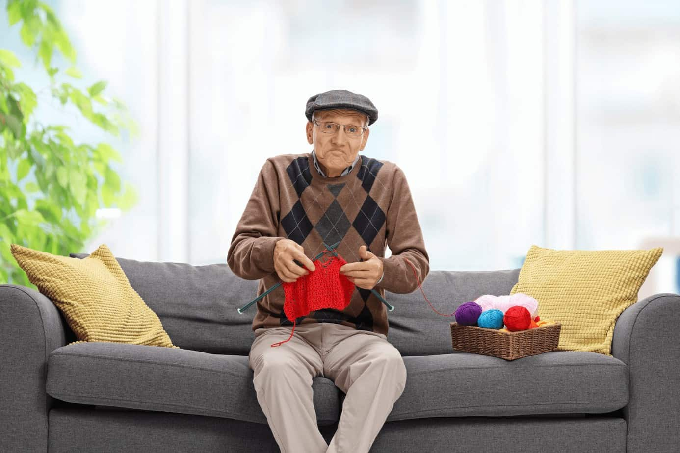 a man with a hat knitting red handkerchief