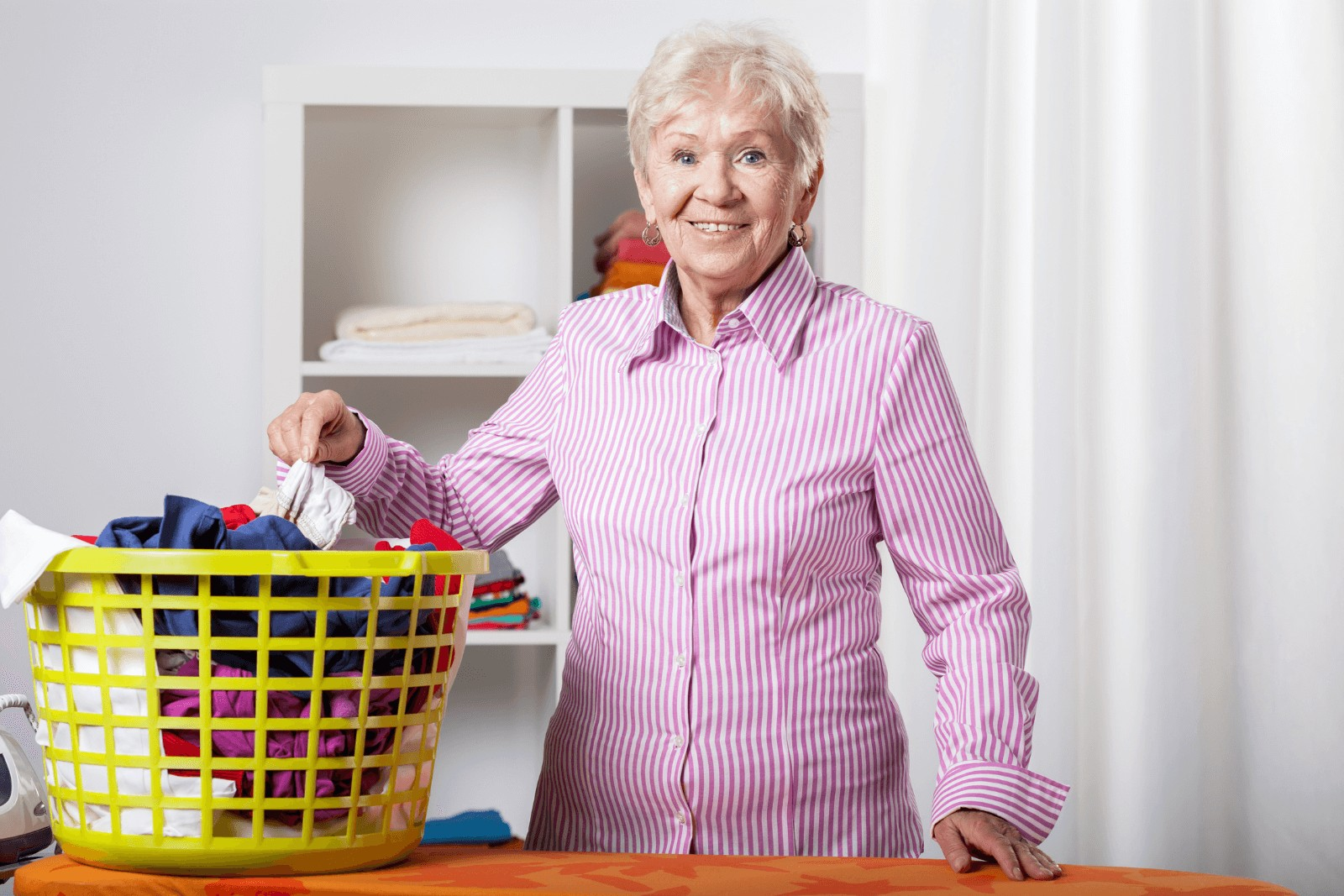 an elderly woman folding some clothes