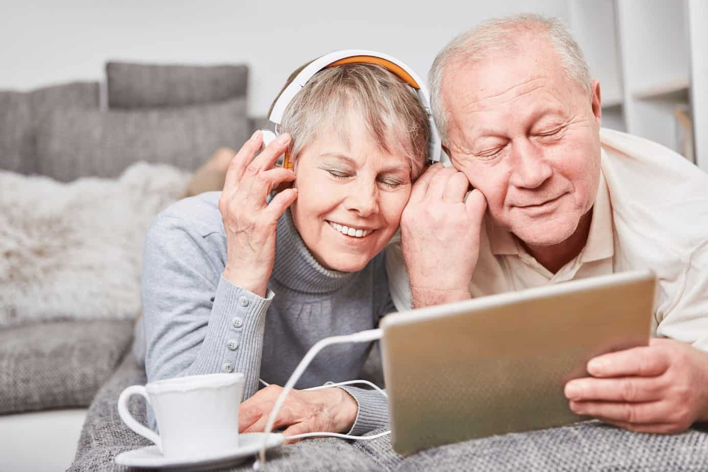 a senior couple listening to old music using a tablet and headset