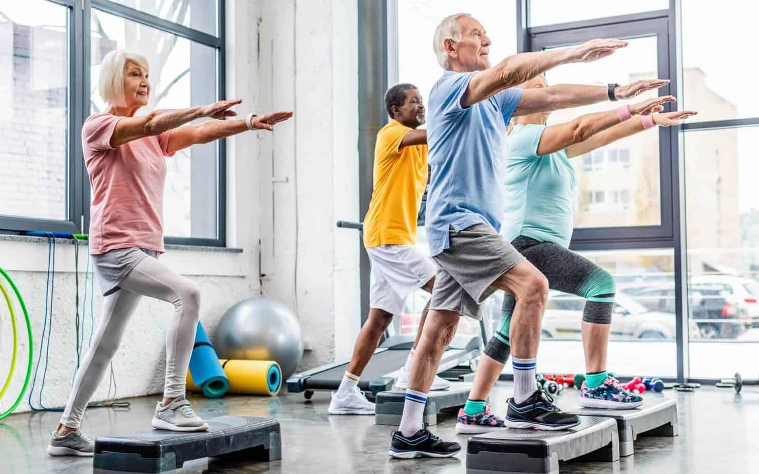 Senior athletes doing hiit workouts on step platforms at gym