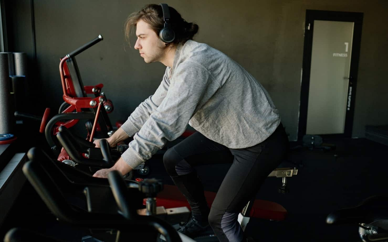 man using an exercise bike at the gym for hiit workout for seniors