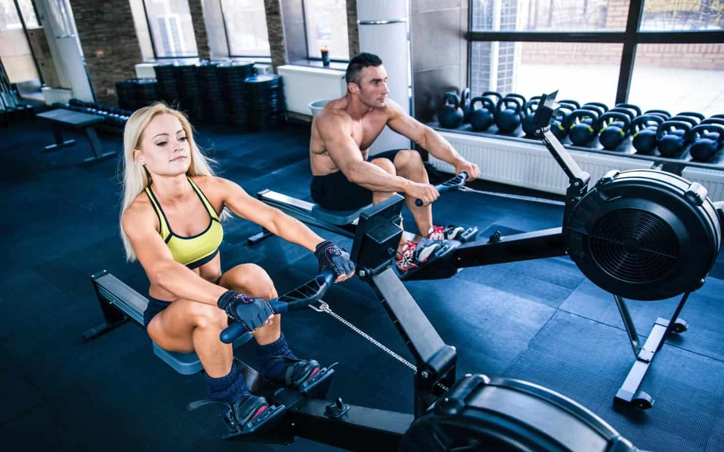 muscular man and sporty woman doing rowing hiit workouts on training simulator in crossfit gym
