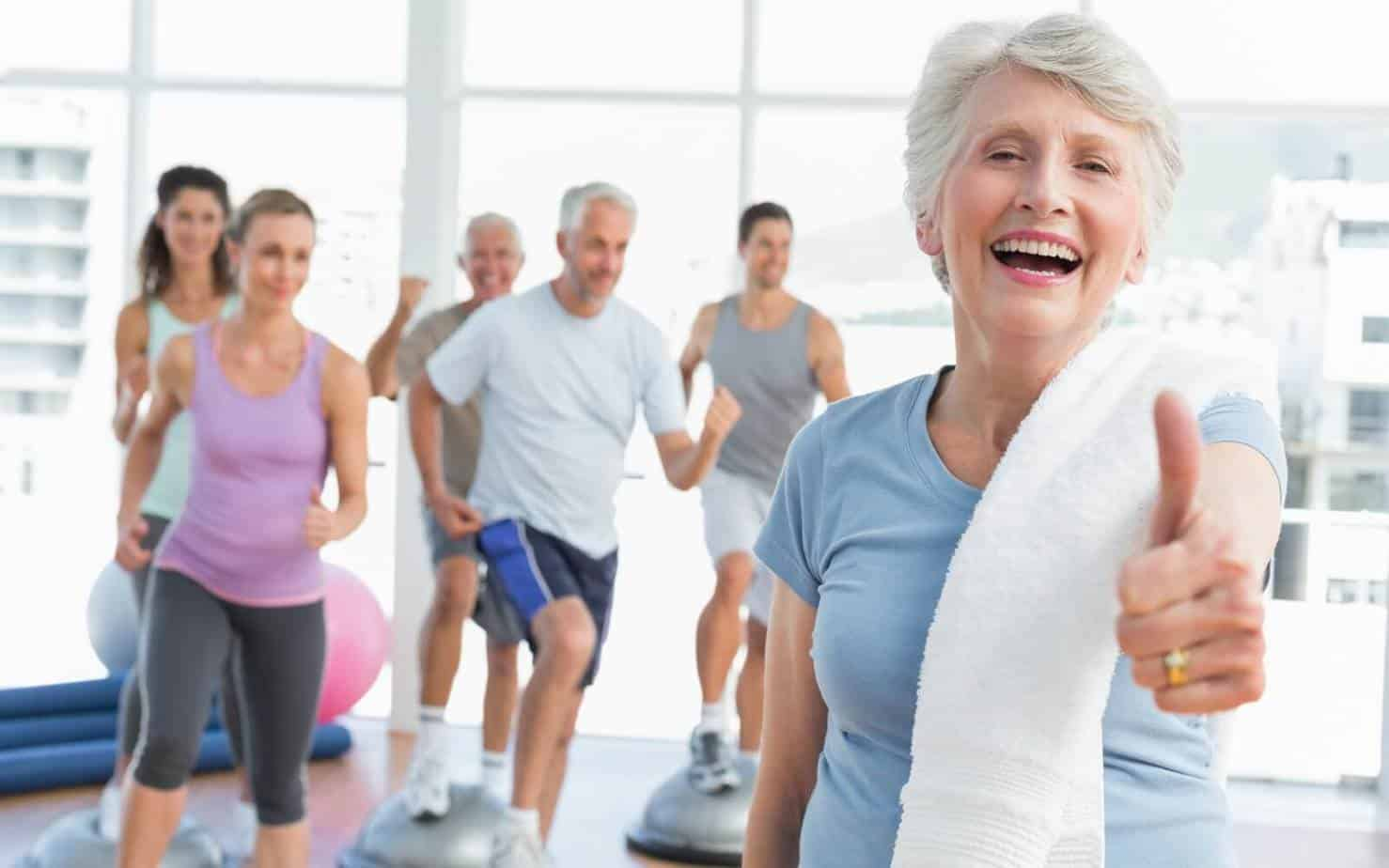 Cheerful senior woman gesturing thumbs up with people doing hiit workout at fitness studio