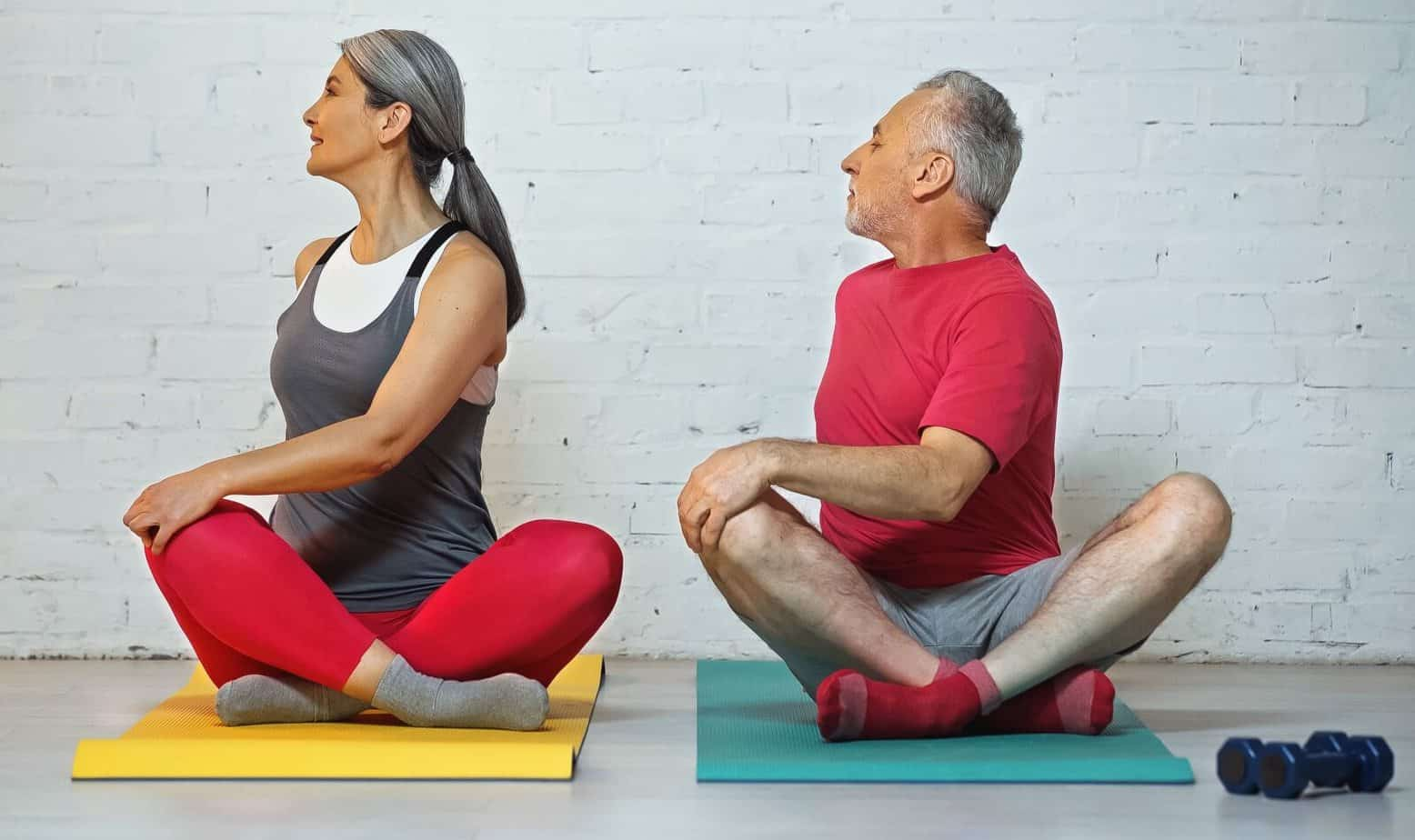 Grey haired senior couple sitting on fitness mats in lotus pose as their posture exercise for seniors