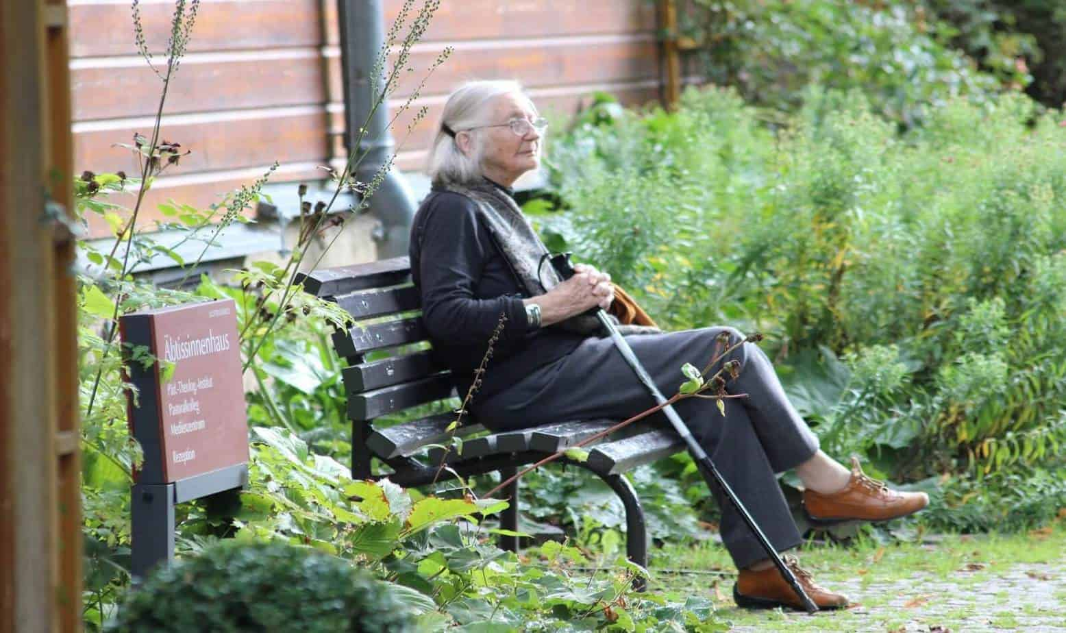 a senior woman sitting on a chair with her crane