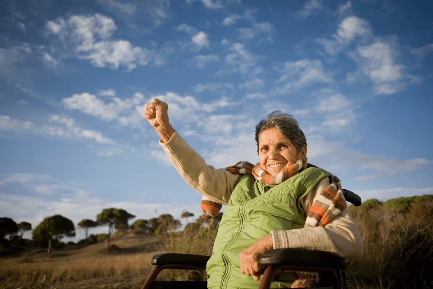 a senior lady raising her hands while traveling with her wheelchair