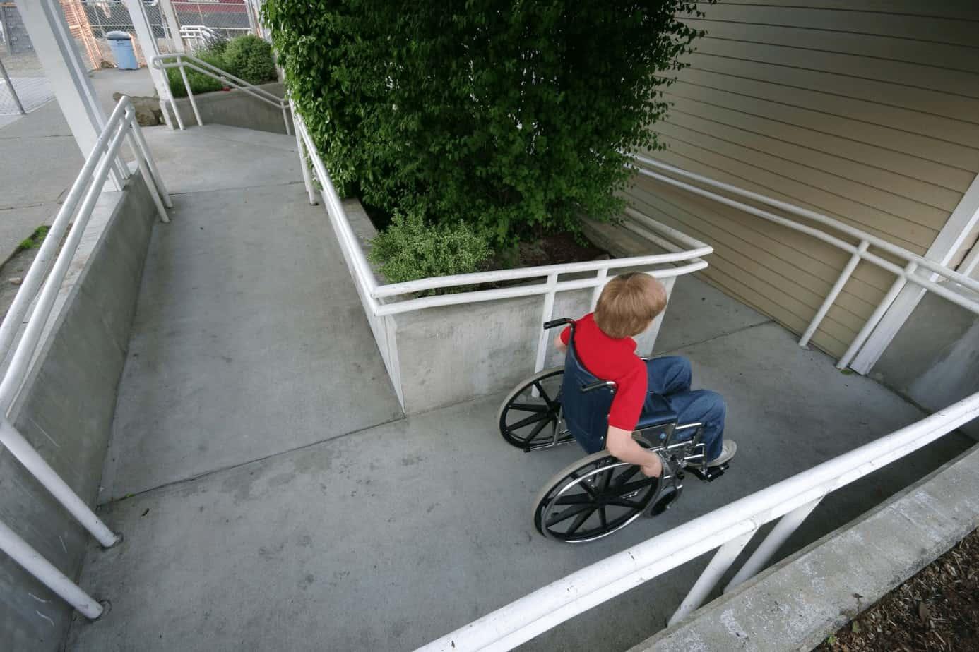 little boy using passing a wheelchair ramp