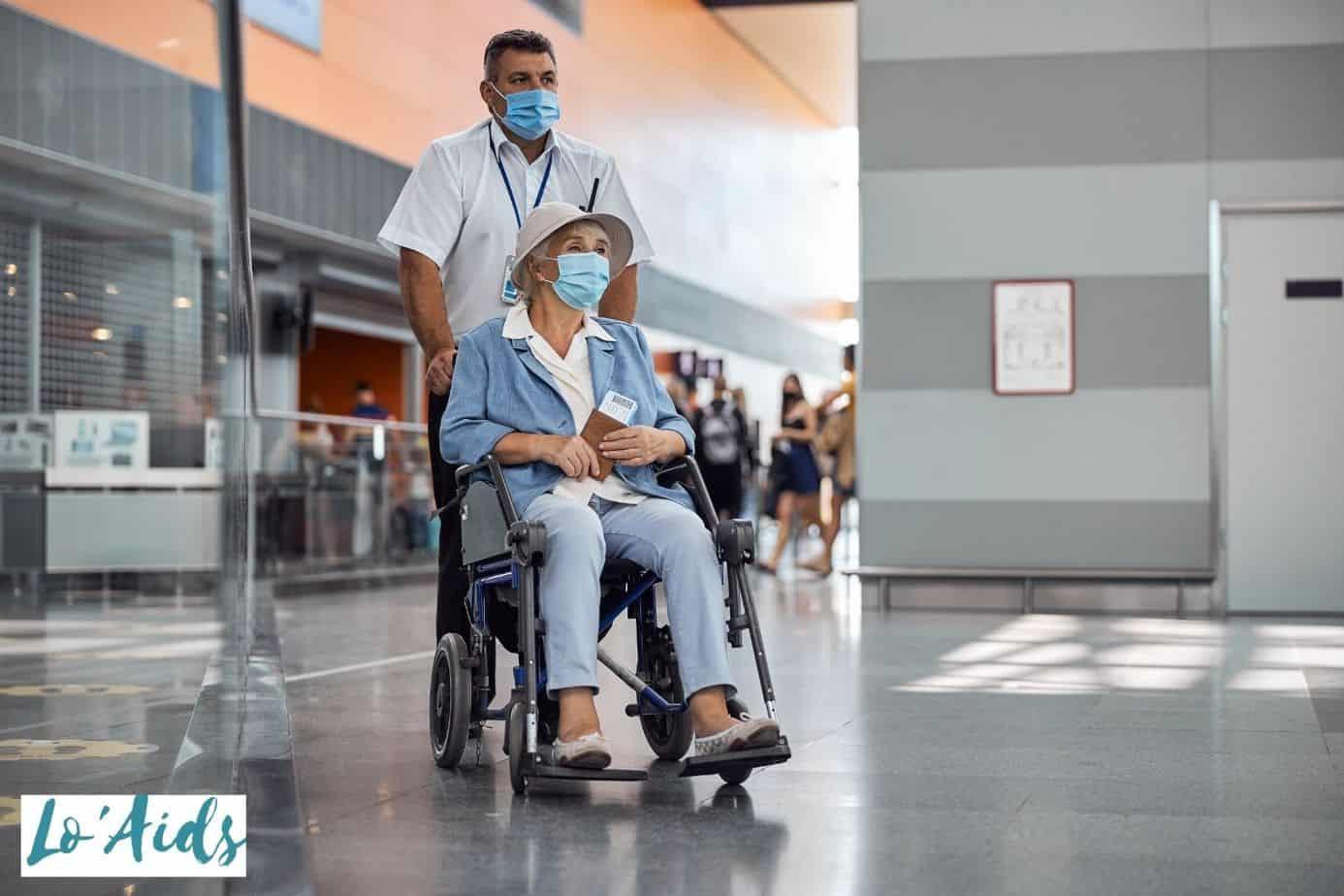 hospital staff pushing a senior in a transport wheelchair