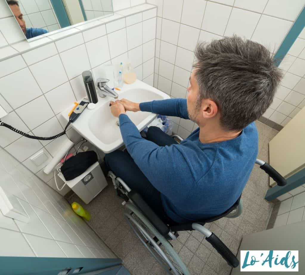 man in a wheelchair washing his hands