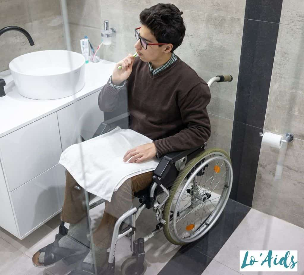 the man in a wheelchair is brushing his teeth beside the sink