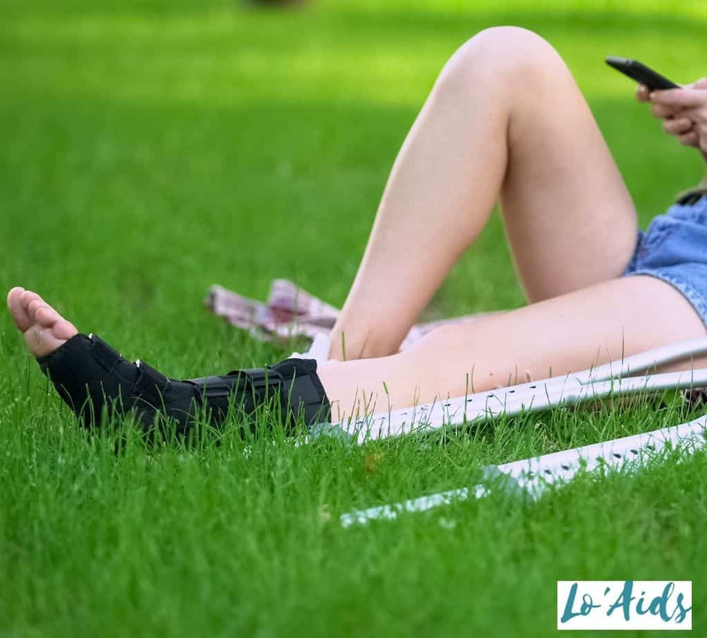lady lying on the grass while wearing an ankle brace