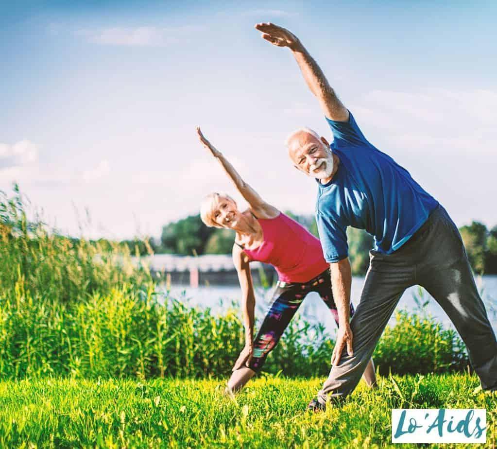 two lovely senior couple exercising beside a lake