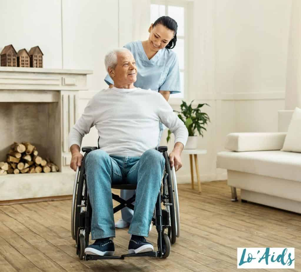 a senior man in a wheelchair being assisted by the nurse