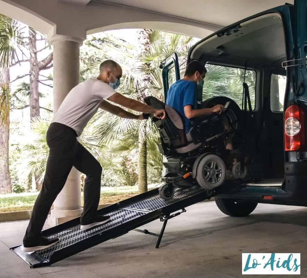 a man pushing the patient in a wheelchair inside the van through a wheelchair ramp