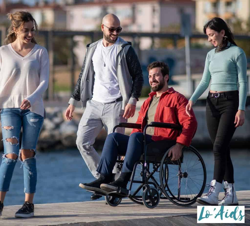 man in a wheelchair strolling with his friends