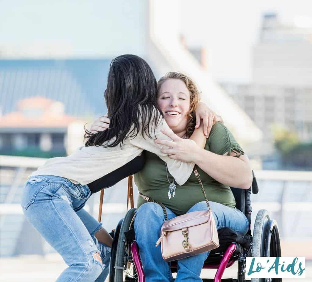 lady embracing her friend in a wheelchair, one of the perks in being in a wheelchair is having nice people around