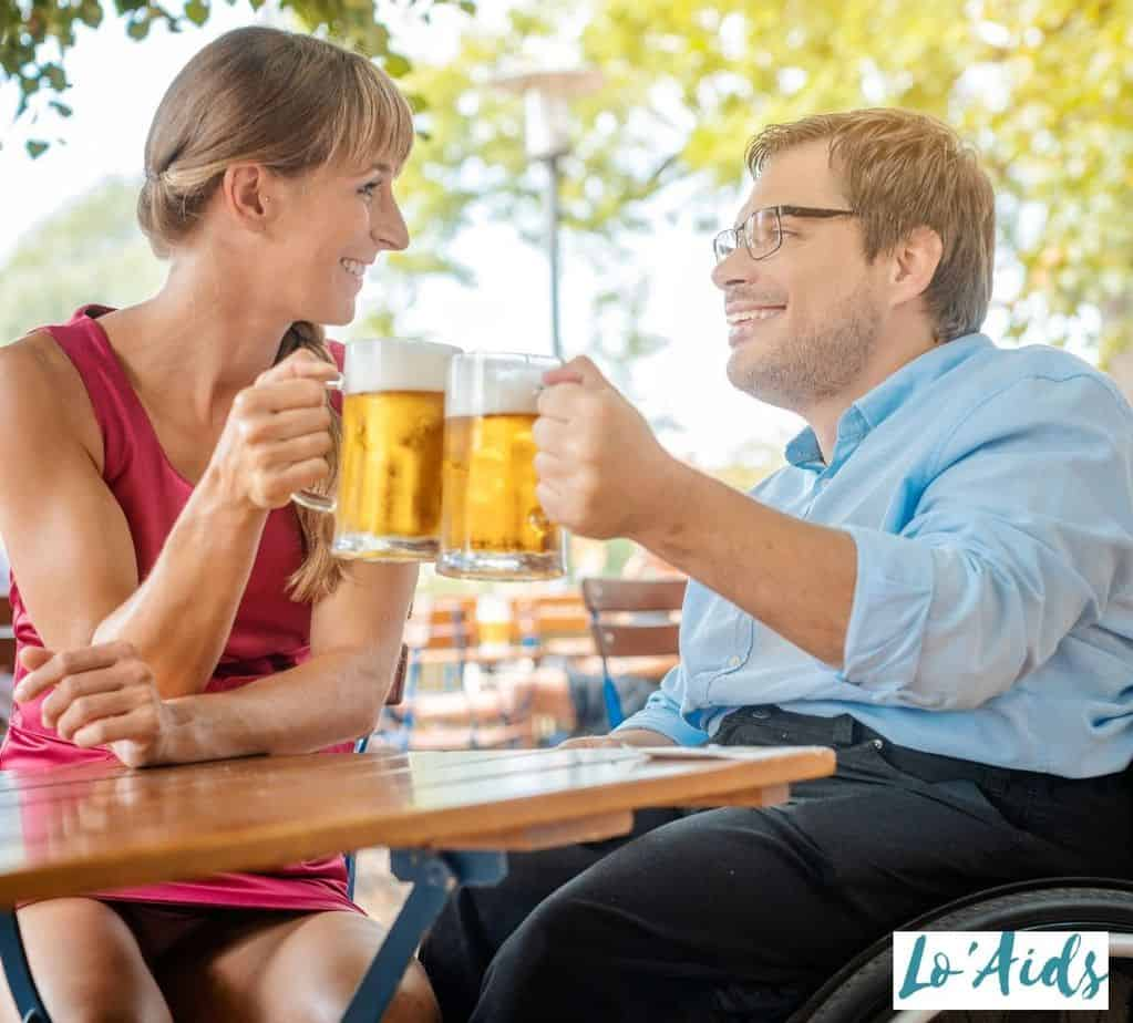 man in a wheelchair drinking beer with a pretty woman