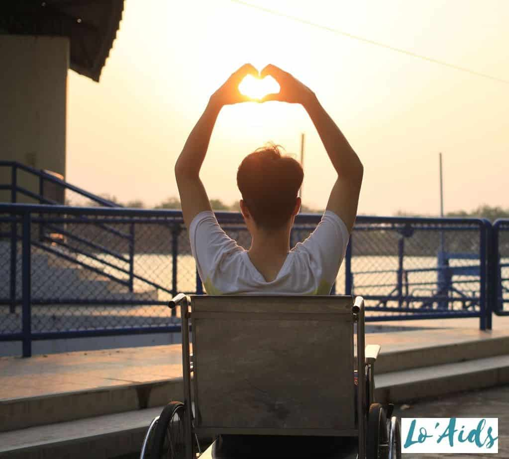 back view of a man in a wheelchair raising a heart hand sign