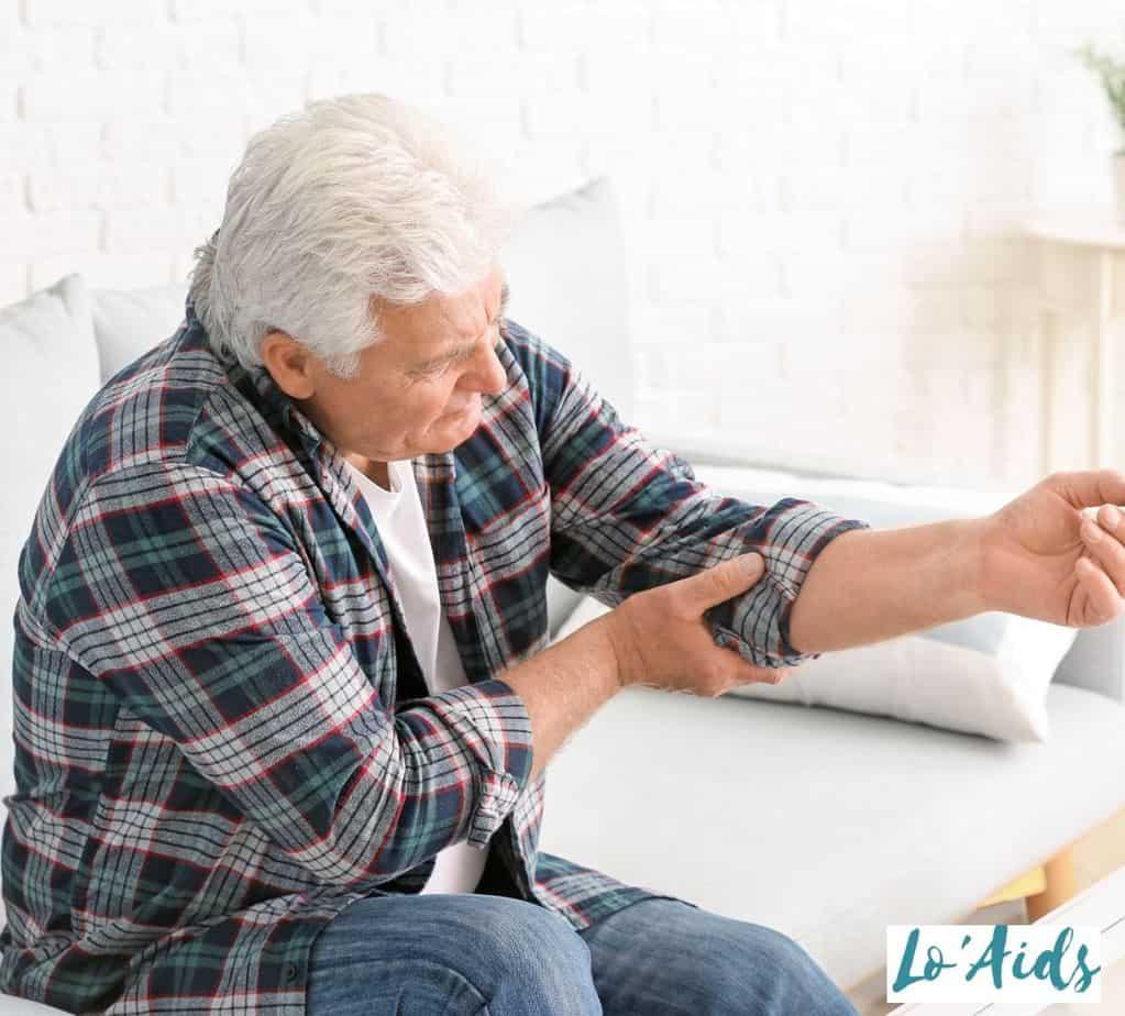 a senior man holding his aching elbow