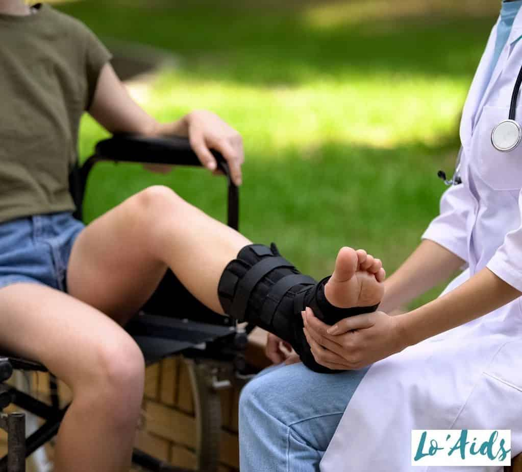 doctor checking the lady's feet with an ankle brace