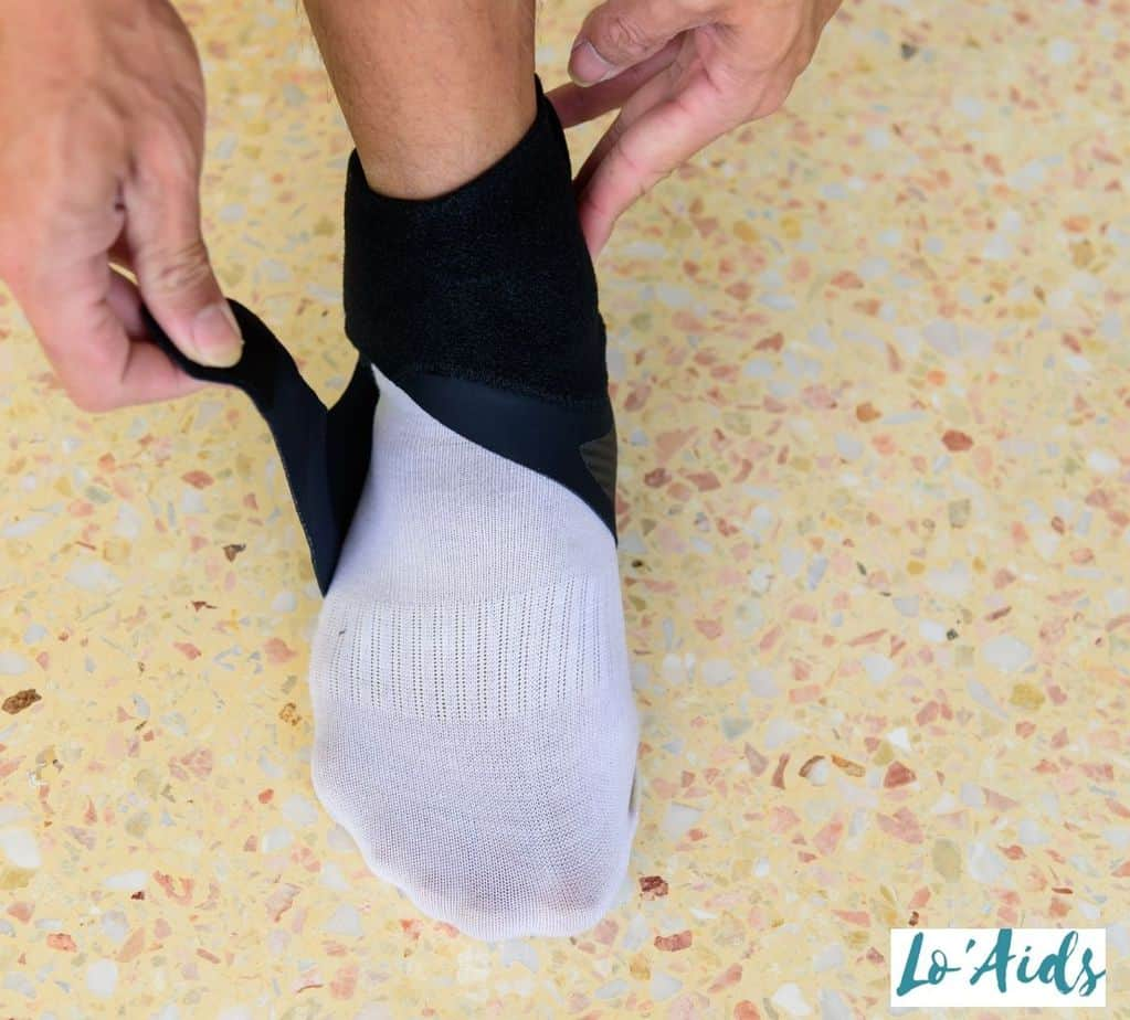 man putting on an ankle brace to his right foot
